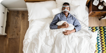 man sleeping in a bed while using a CPAP machine
