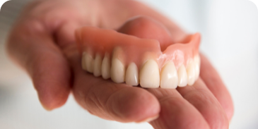 complete upper denture in the palm of a hand