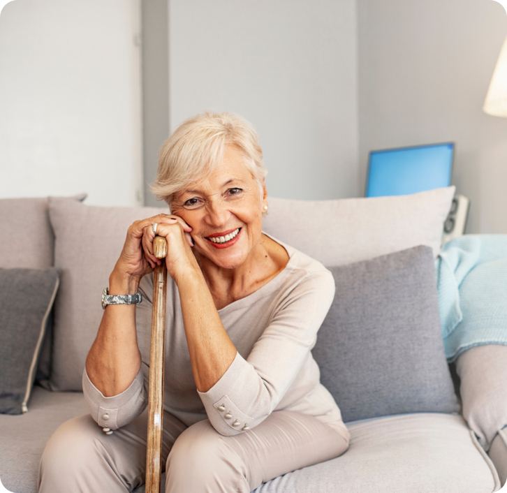 elderly woman with dentures sitting on a couch holding a cane while smiling