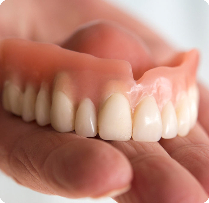 close up of complete upper dentures in the palm of a hand