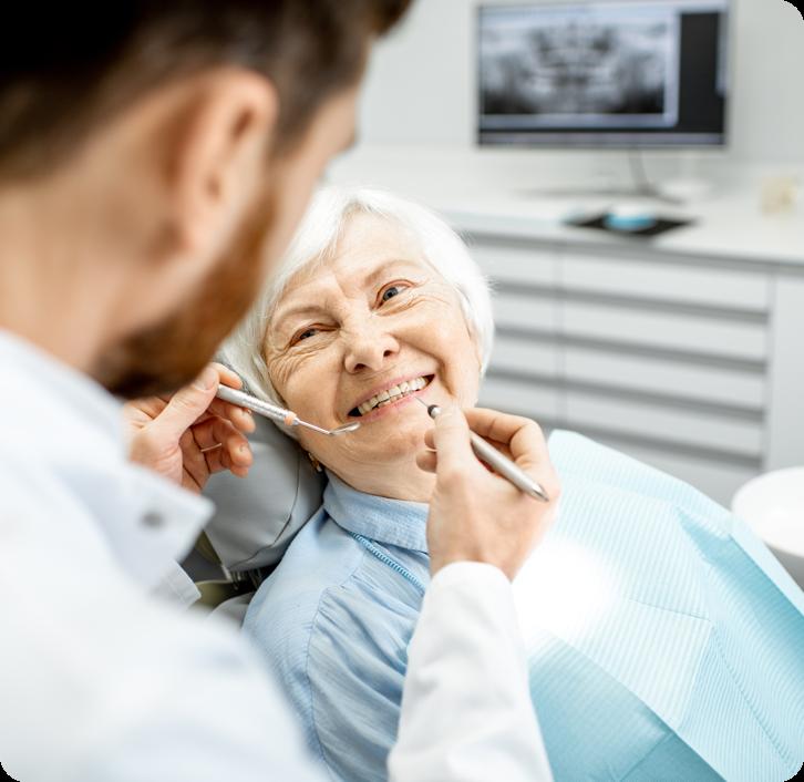 elderly woman smiling at her denturist as he begins to inspect her dentures.