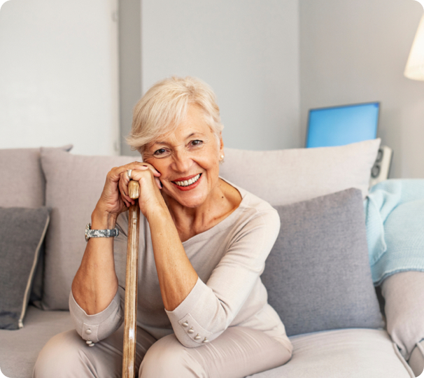 elderly woman with dentures sitting on a couch holding a cane while smiling.