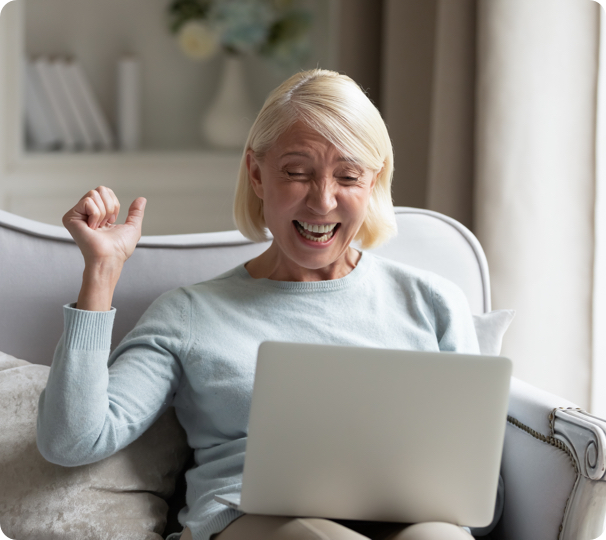 elderly woman looking excited during a video call on her laptop