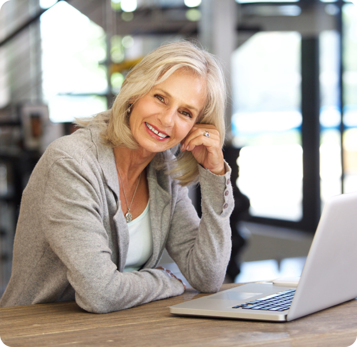 smiling older woman with dentures sitting at a table in front of her laptop