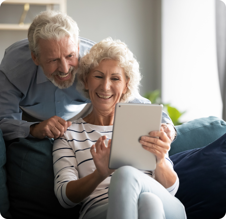 elderly couple with dentures smiling while on a video call on their tablet