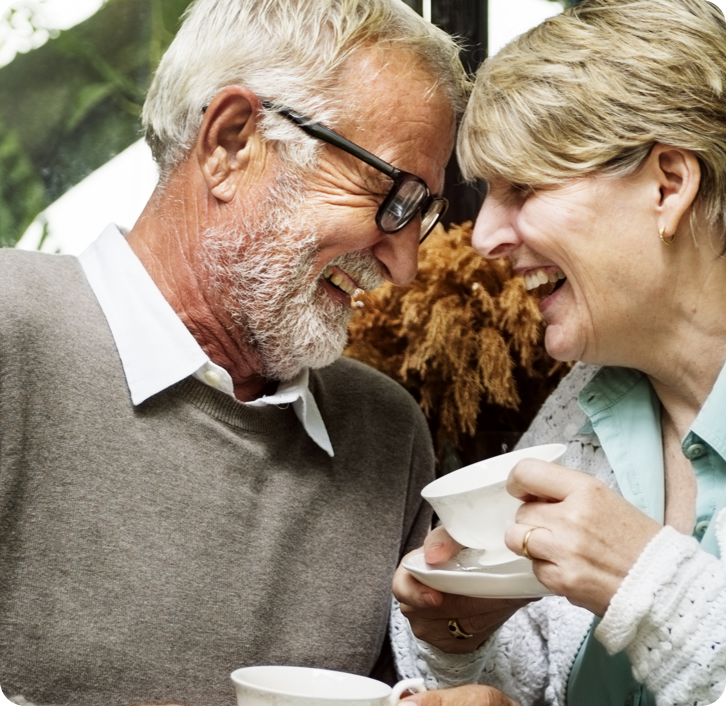 elderly couple with dentures laughing together while they share a cup of tea.