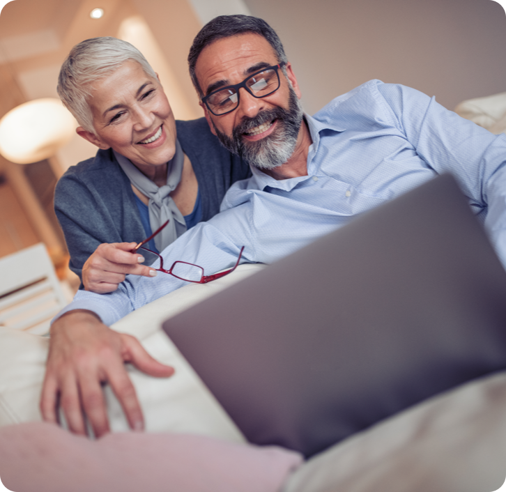 middle aged couple with dentures smiling while on a video call on a laptop