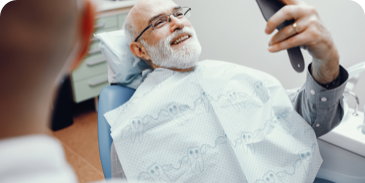 smiling man in a dental chair looking at his new dentures in a mirror