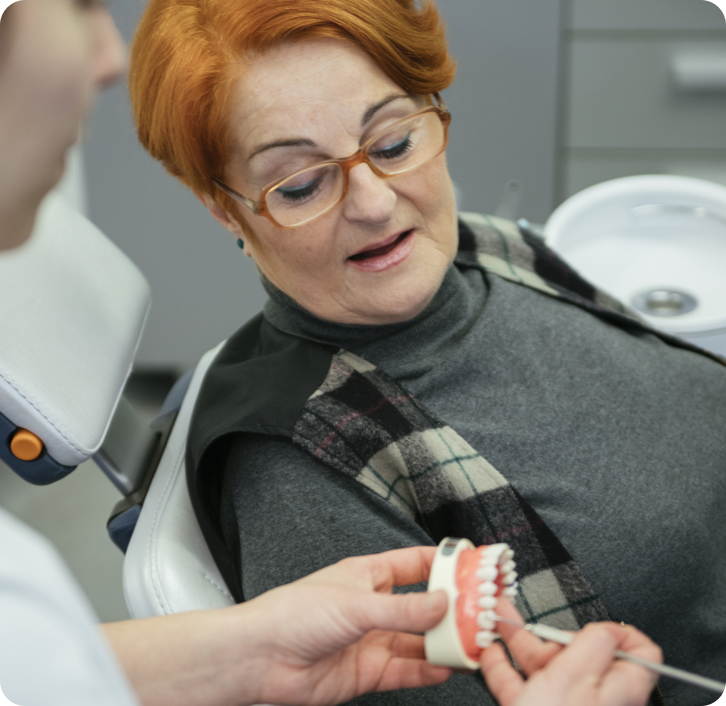 older woman sitting in a dental chair while the denturist shows her a model.