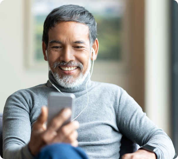 middle aged man with dentures smiling while on a video call on his phone.