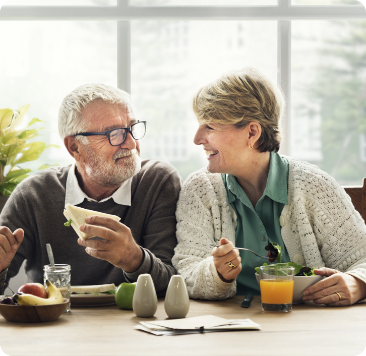 elderly couple with dentures enjoying a meal together.