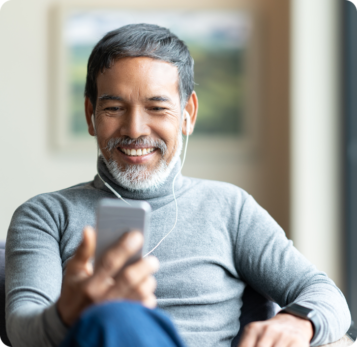 middle aged man with dentures smiling while on a video call on his phone