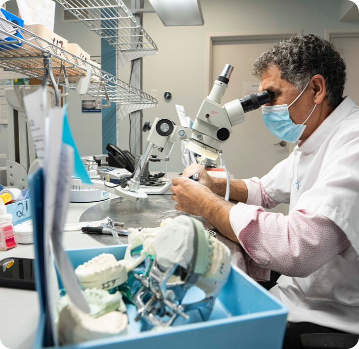 denturist looking in a microscope while making a new denture