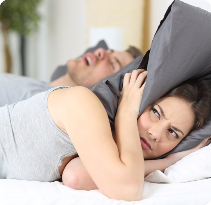 woman covering her ears with a pillow while a man snores in the background.