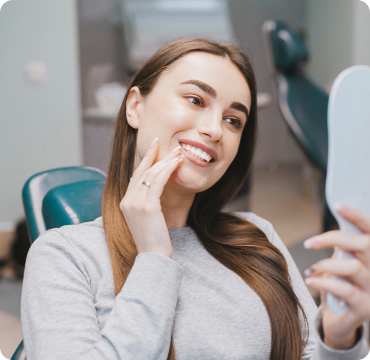 Woman checking out her smile in a mirror after teeth whitening