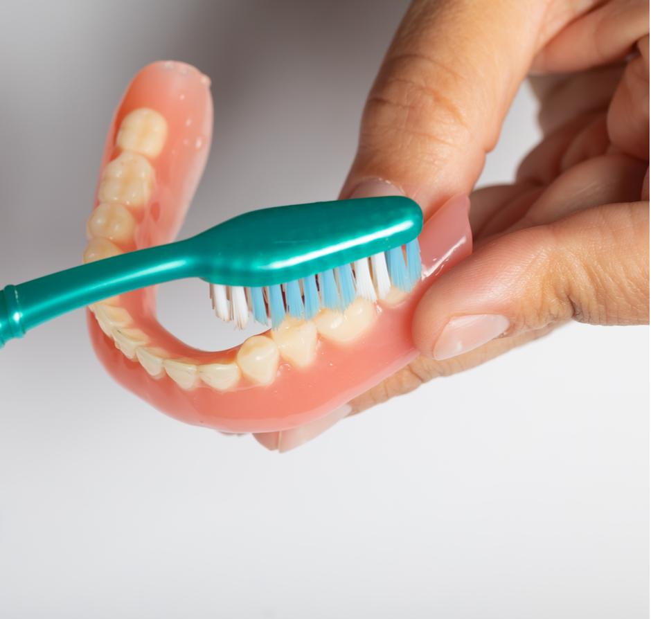 brushing dentures with toothbrush