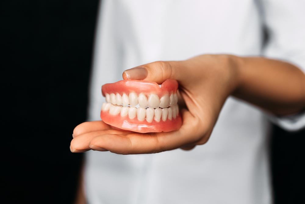 denturist holding a pair of new dentures