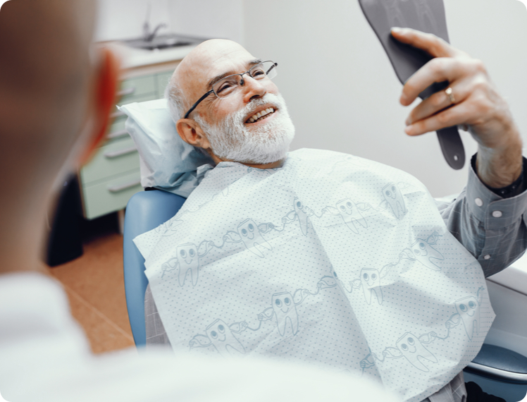 man in a dental chair looking at his new dentures in a mirror
